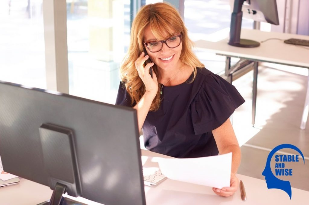 Dealing with recruiters: A woman sitting at her desk taking a recruiter call