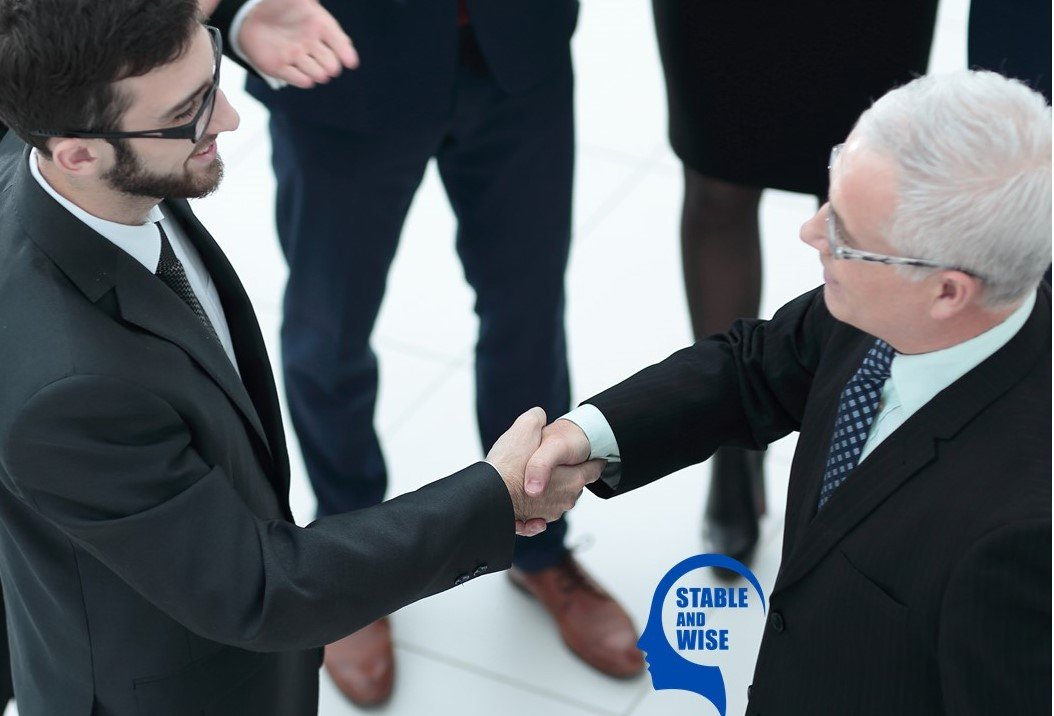 Ageism; mature aged worker shaking hands with younger worker
