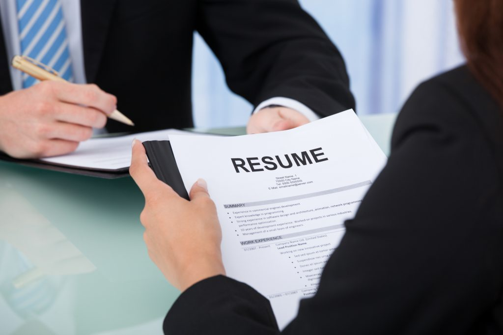 Resume Guide: Older female candidate holding resume at a desk during interview