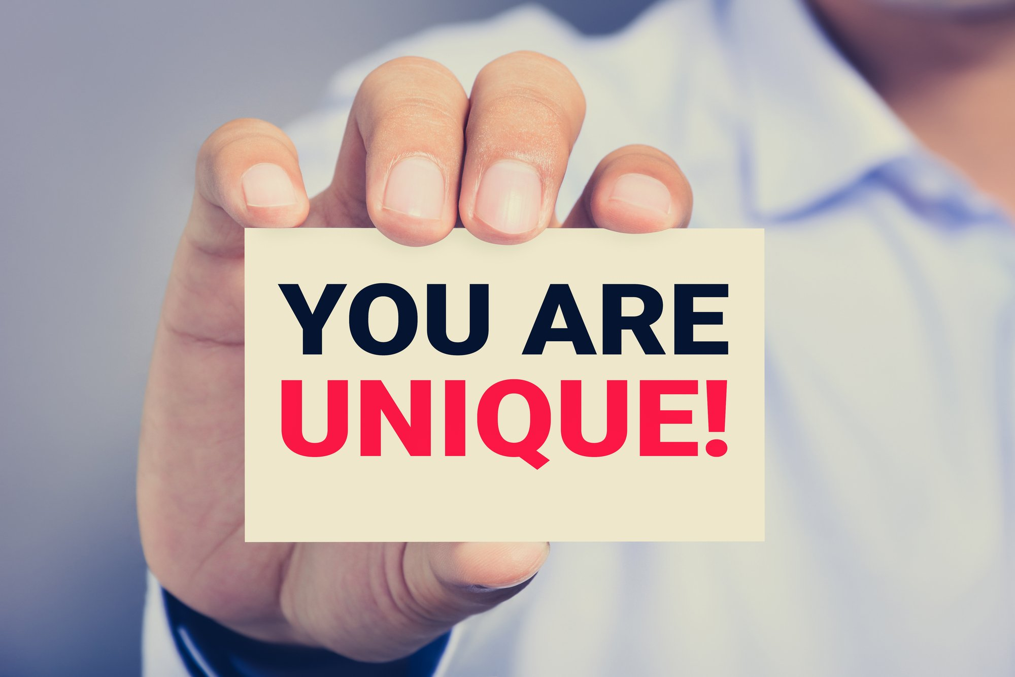 Gettiing a job in your 50's: a worker holding a 'YOU ARE UNIQUE!' sign